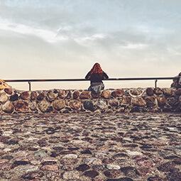 girl looking sea sky clouds rock stones solitude travel real social UGC photography